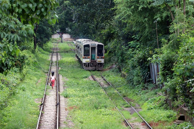 Behind of Myanmarese lady villager walking on the railroad tracks. Parallel with another rail, the train is running. stock photo