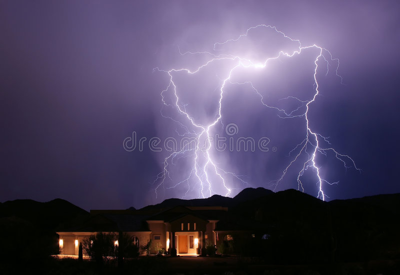 Behind The Neighbors. Lightning strikes behind the neighbor's home in the hills outside of Phoenix, Arizona royalty free stock image