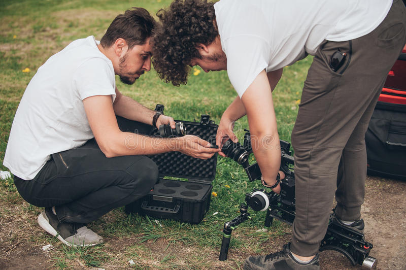 Behind the scene. Cameraman and assistant changes lens on camera stock photography