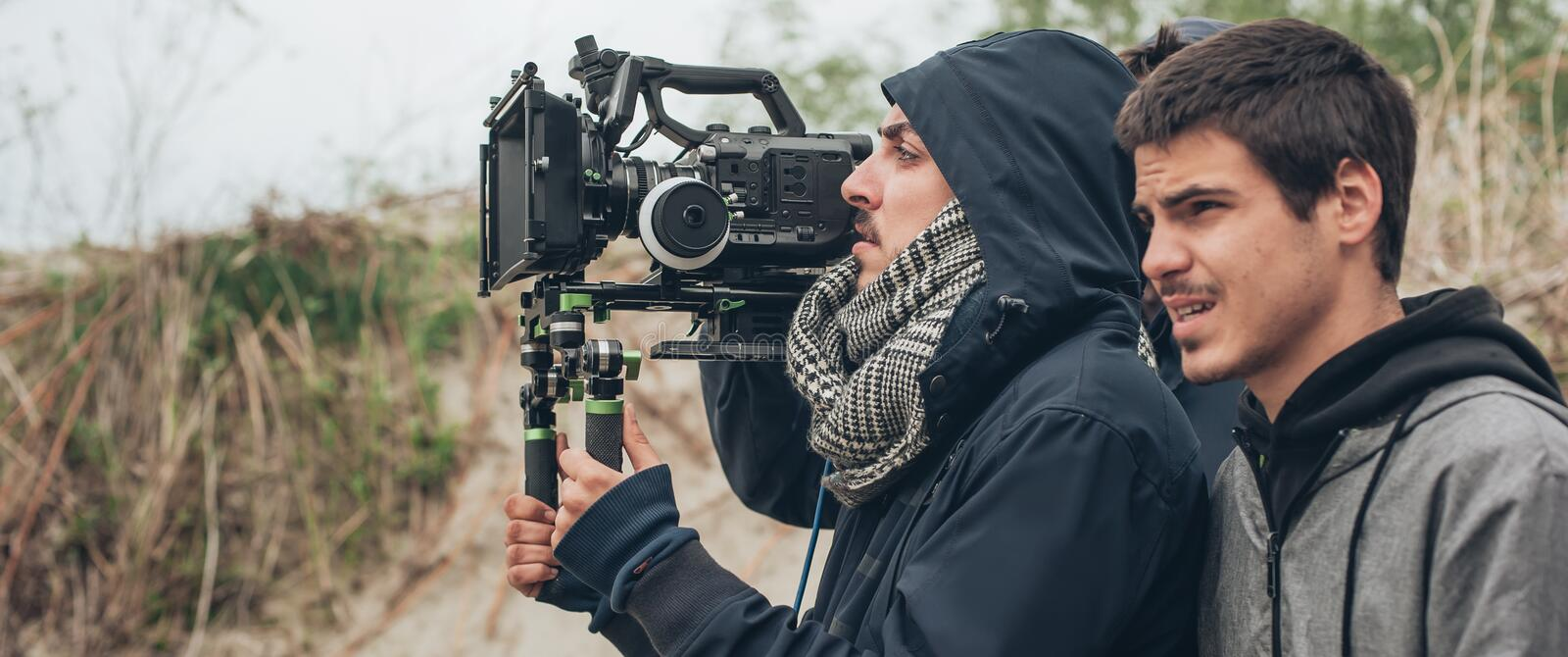 Behind the scene. Cameraman and film director shooting film scene stock photos