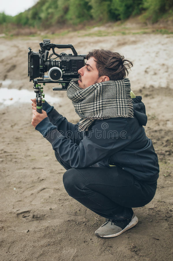 Behind the scene. Cameraman shooting film scene with his camera royalty free stock images