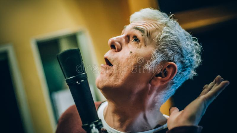 Behind scene. Famous alternative male singer practice singing on microphone stock image