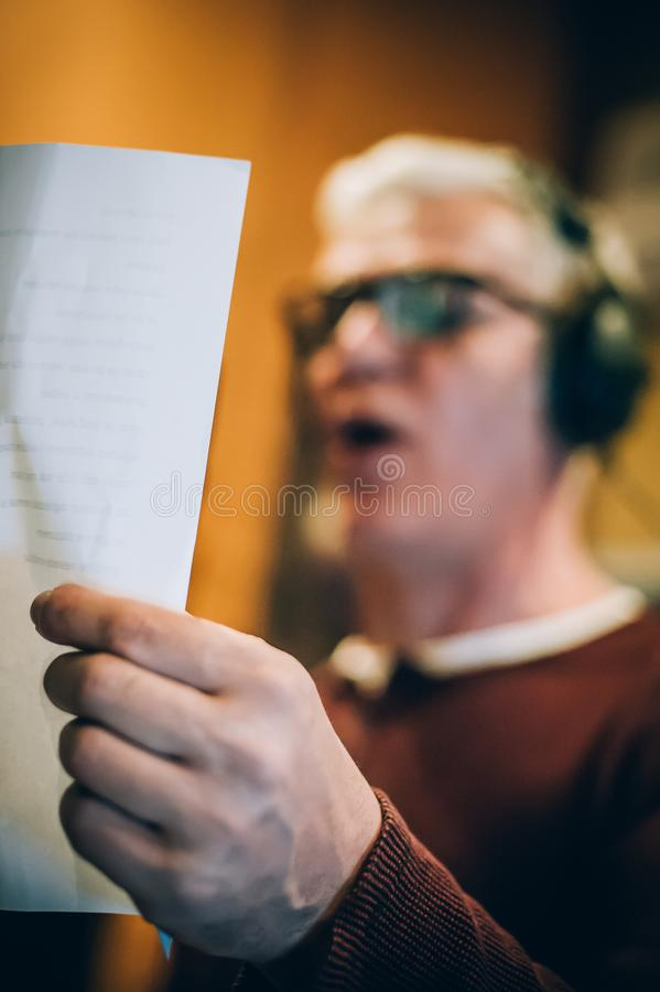 Behind scene. Famous alternative male singer practice singing on microphone. Behind the scene. Famous alternative male singer practice singing on the microphone royalty free stock photo