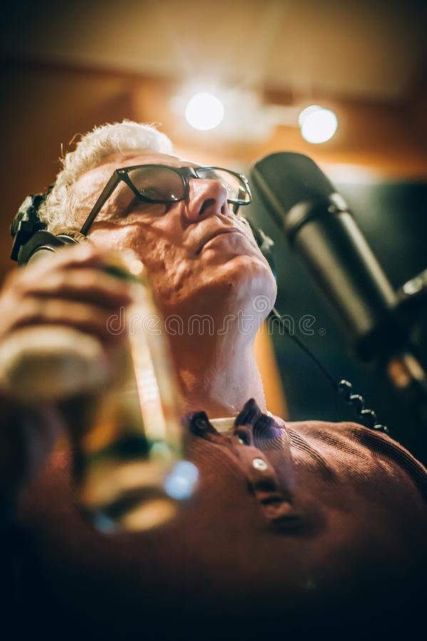 Behind scene. Famous alternative male singer practice singing on microphone stock photography
