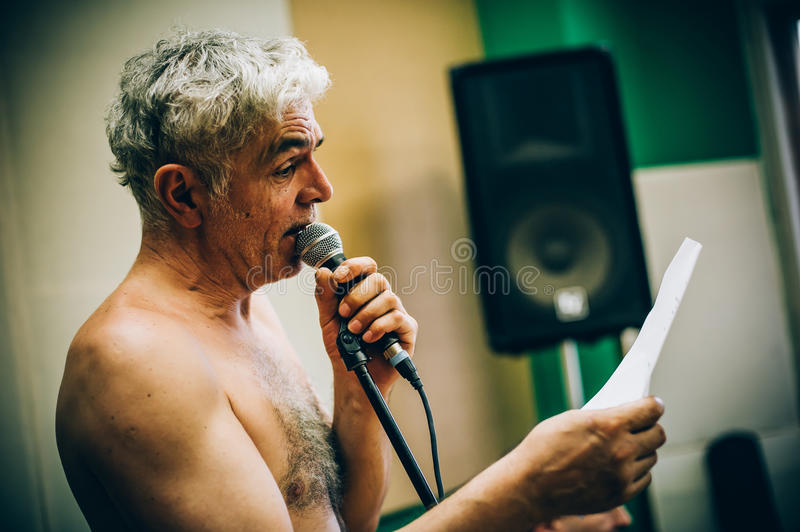 Behind scene. Famous alternative male singer practice singing on. Behind the scene. Famous alternative male singer practice singing on the microphone in the stock photo