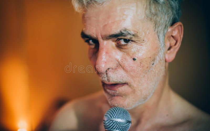 Behind scene. Famous alternative male singer practice singing on. Behind the scene. Famous alternative male singer practice singing on the microphone in the royalty free stock photos