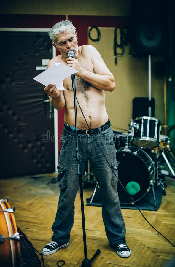 Behind scene. Famous alternative male singer practice singing on. Behind the scene. Famous alternative male singer practice singing on the microphone in the royalty free stock images