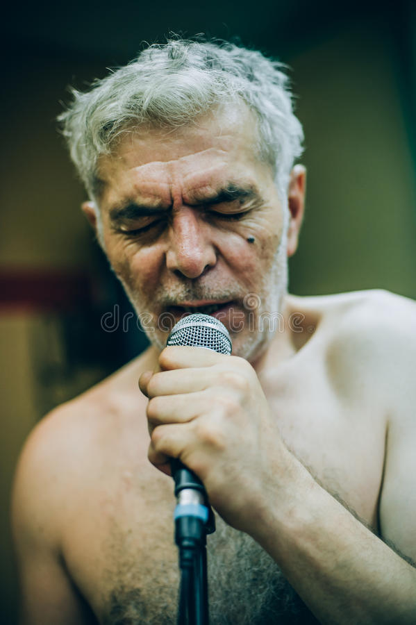 Behind scene. Famous alternative male singer practice singing on. Behind the scene. Famous alternative male singer practice singing on the microphone in the stock photos
