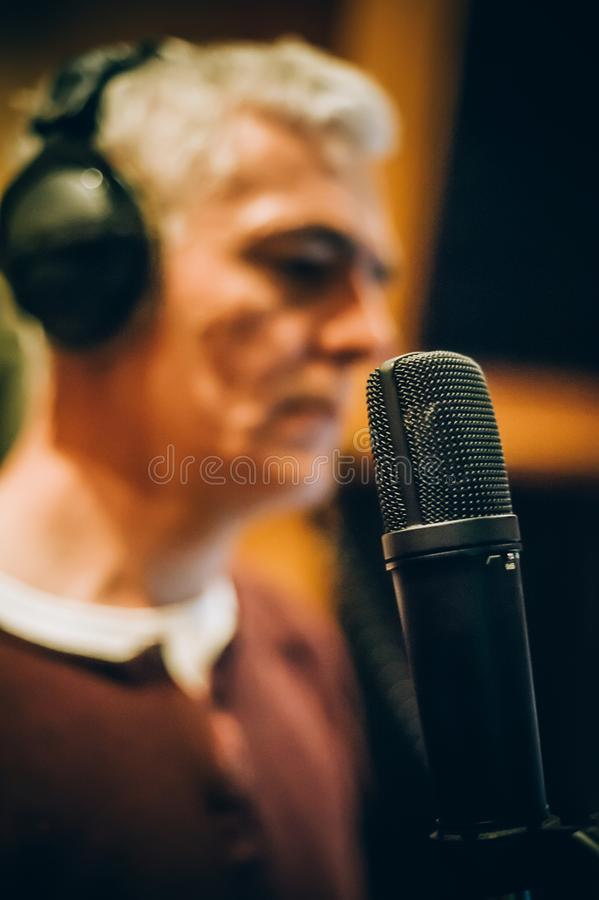 Behind scene. Famous alternative male singer practice singing on microphone stock photos