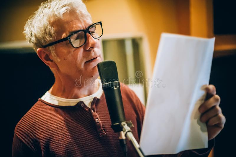 Behind scene. Famous alternative male singer practice singing on microphone royalty free stock photo
