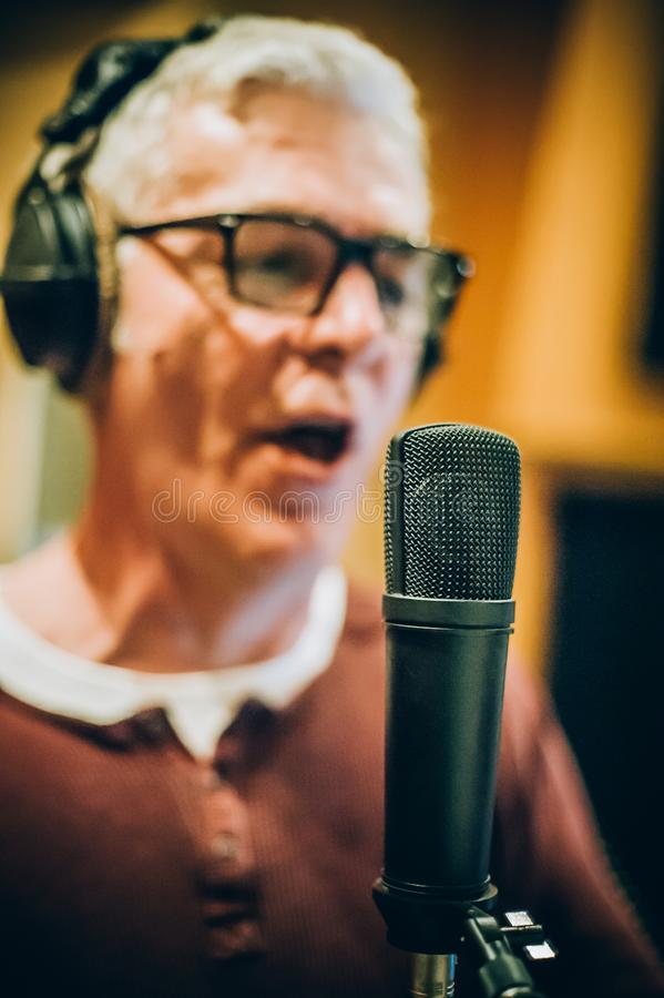 Behind scene. Famous alternative male singer practice singing on microphone stock photo