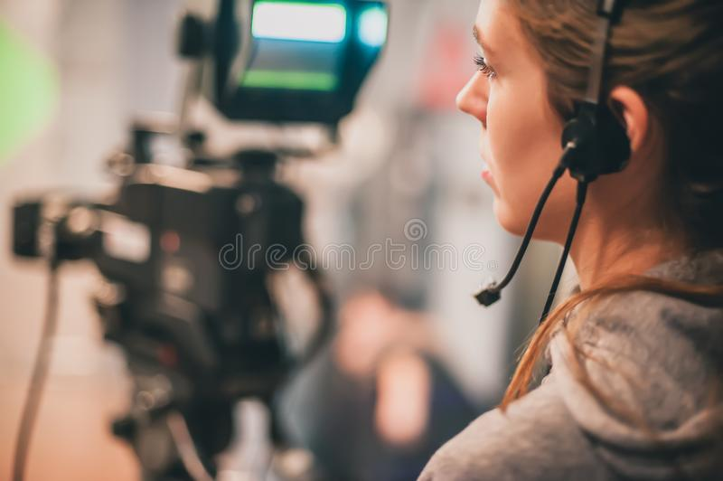 Behind the scene. Female cameraman shooting film scene with came stock image