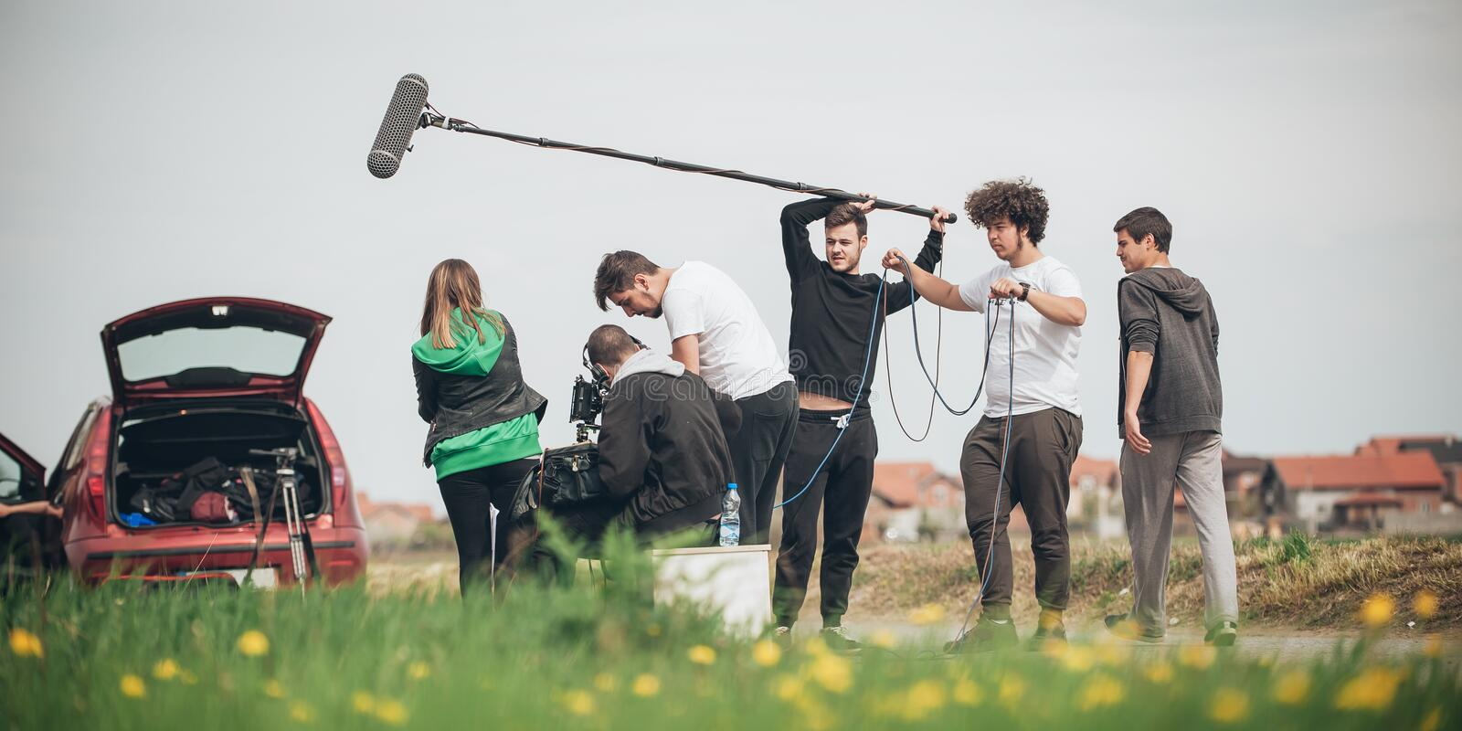 Behind the scene. Film crew filming movie scene outdoor. Behind the scene. Film crew team filming movie scene on outdoor location. Group cinema set stock images