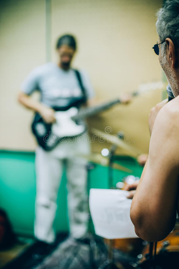 Behind scene. Rock band practice in messy recording music studio. Behind the scene. Rock band practice in the messy recording music studio. Alternative musician stock images