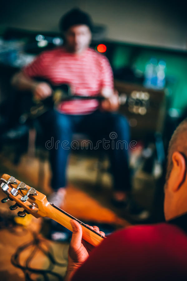 Behind scene. Rock band practice in messy recording music studio. Behind the scene. Rock band practice in the messy recording music studio. Alternative musician royalty free stock photo