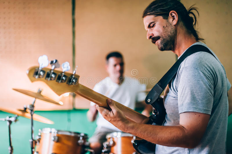 Behind scene. Rock band practice in messy recording music studio. Behind the scene. Rock band practice in the messy recording music studio. Alternative musician royalty free stock photography