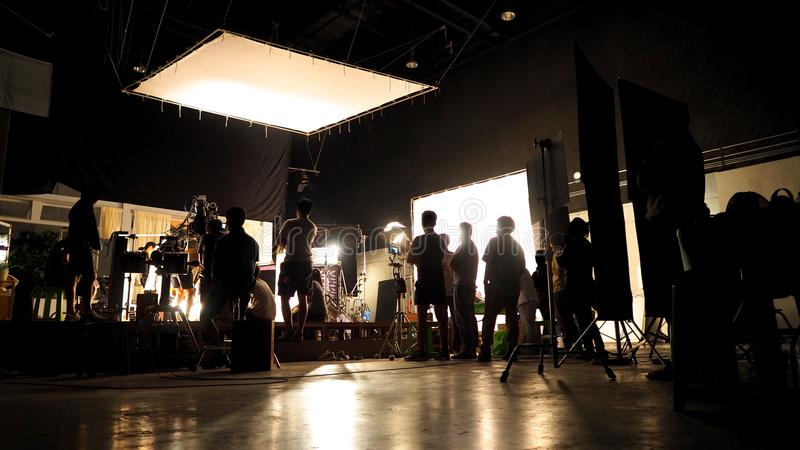 Behind the scenes of video shooting production crew team silhouette. And camera equipment in studio stock photos