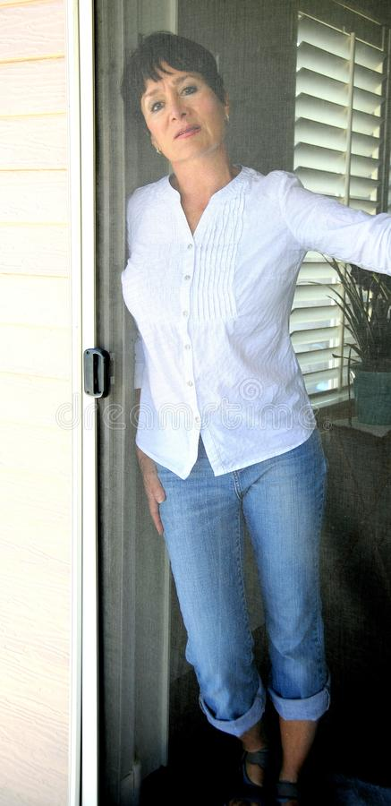 Behind the screen door expressions. Mature female beauty standing behind a screen door on the patio deck royalty free stock photos