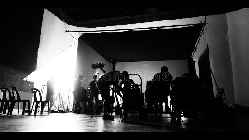 Behind the shooting production crew team and silhouette of camera and equipment in studio stock photo