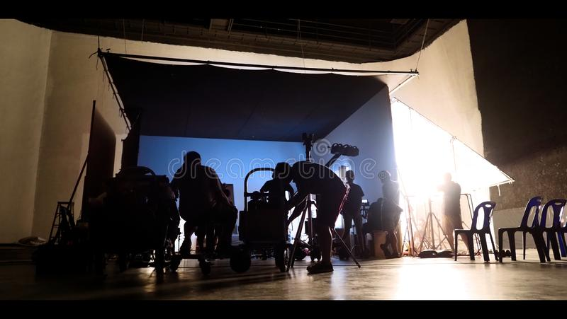 Behind the shooting production crew team and silhouette of camera and equipment in studio stock photography