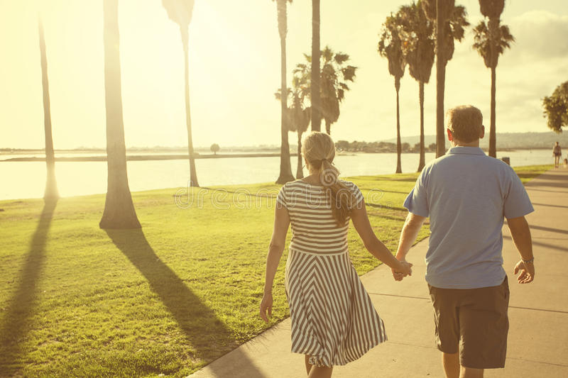 Behind view of a middle aged couple walking together holding hands. Middle aged couple walking together holding hands along the beach boardwalk. Building stock photography