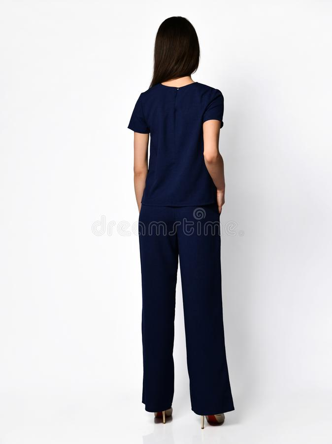 From behind. Young beautiful woman posing in new dark blue blouse with pants fashion casual summer costume stock images