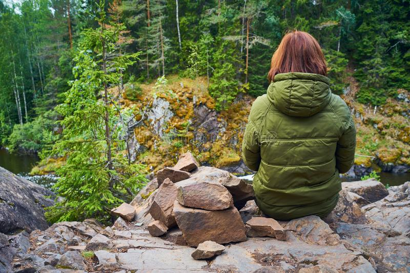 Behind of young woman admires the Northern nature. Person sitting on background of rocks, stones, rear view. Behind of young woman admires the Northern nature royalty free stock photo