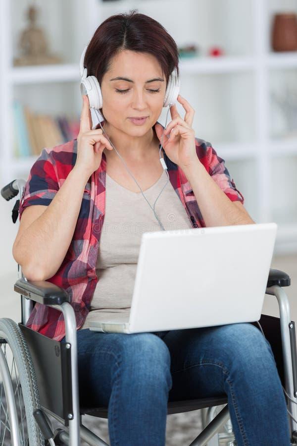 Behinderte Frau, die zu Hause Laptop-Computer verwendet lizenzfreies stockfoto