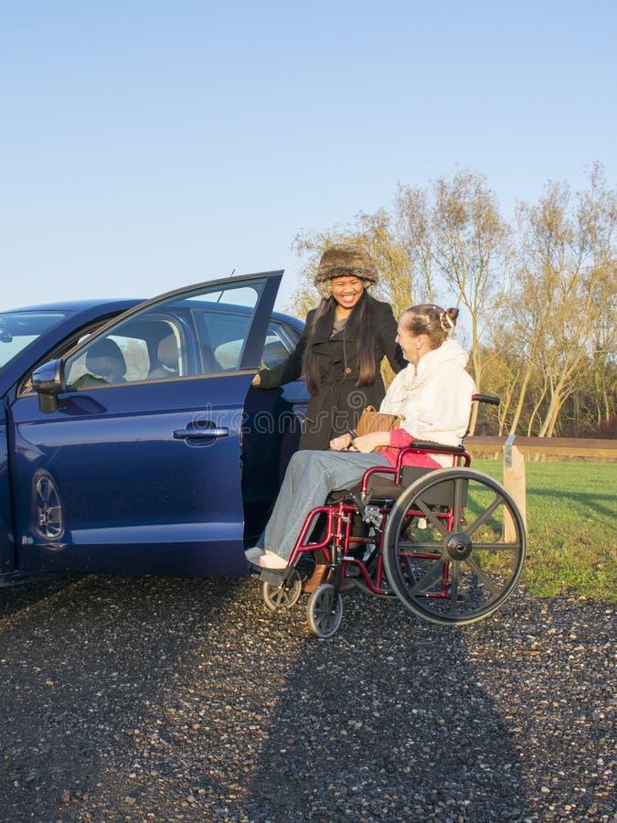 Behinderte Frau im Rollstuhl mit dem Betreuer, der in Mobilitäts-Auto kommt stockfotos