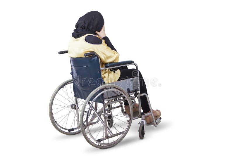 Behinderte Frau schaut mit einem Rollstuhl traurig stockfotografie