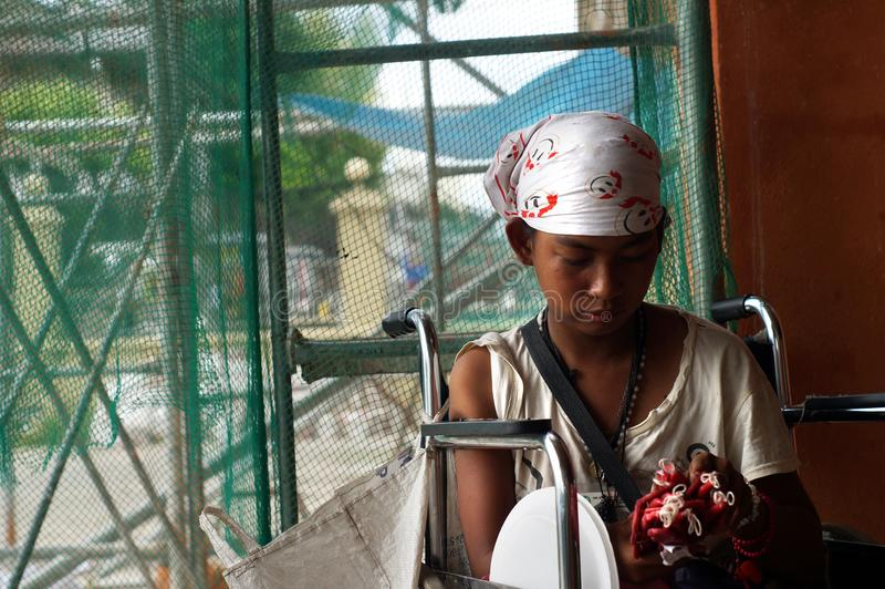 Behinderte junge Dame im Rollstuhl verkauft Kerzen am Kirchenportal stockfotografie
