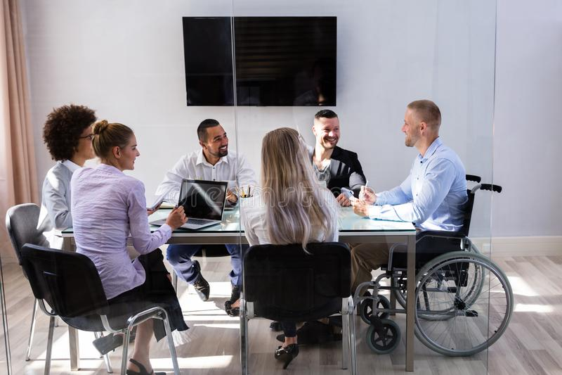 Behinderte Manager-Sitting With His-Kollegen lizenzfreie stockbilder