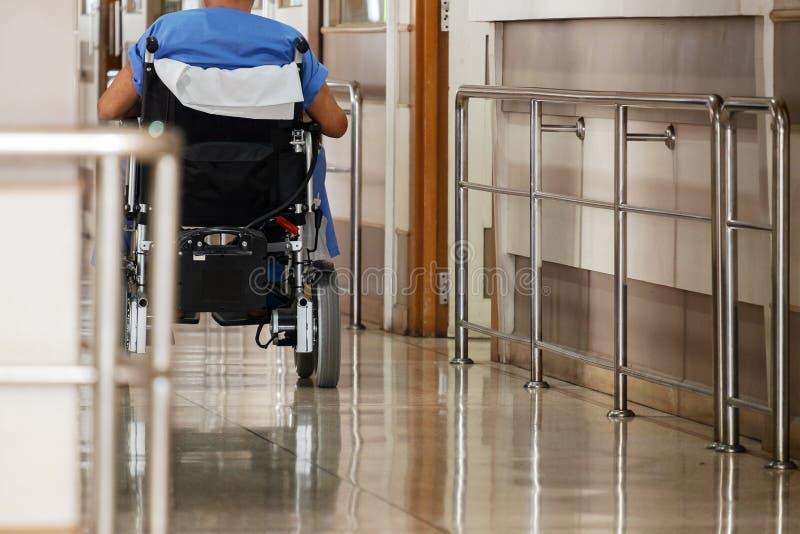 Behinderter alter Mann, der durch einen elektrischen Rollstuhl beim Hospita umzieht stockbilder