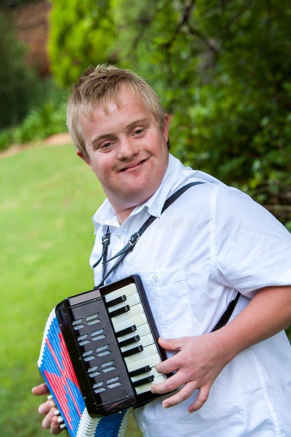 Behinderter Junge, der das Akkordeon spielt. stockfoto