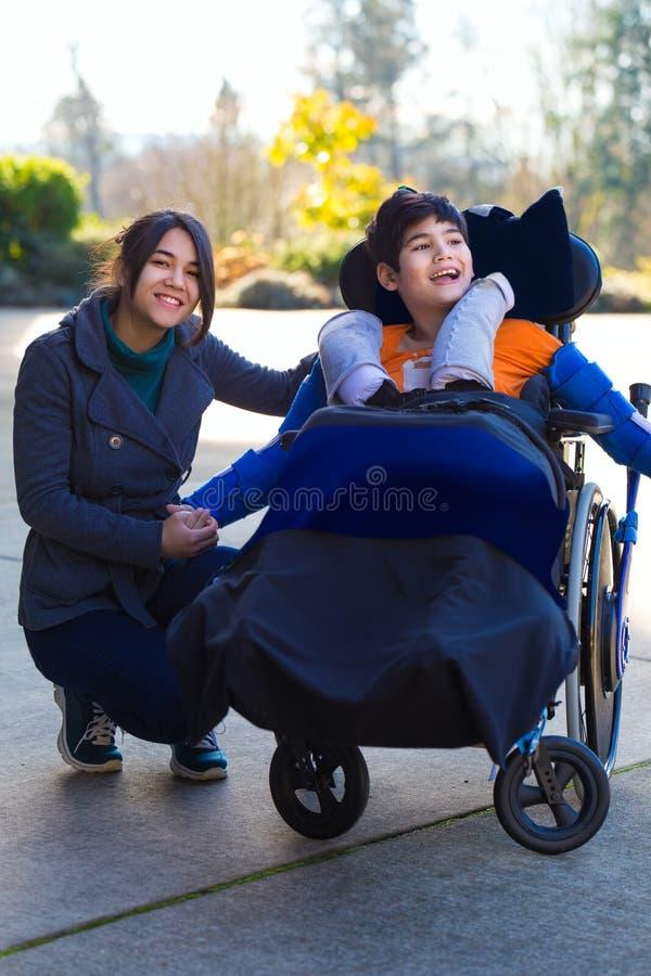 Behinderter Junge im Rollstuhl, der draußen mit seiner Pflegekraft sitzt stockfotografie