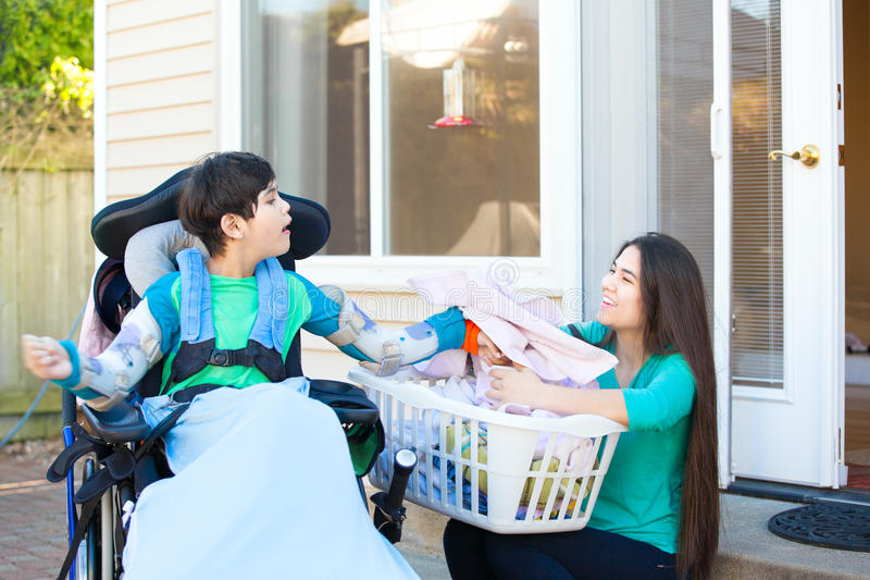 Behinderter Junge in Schwester-Faltenwäscherei des Rollstuhls helfender älterer stockfotografie