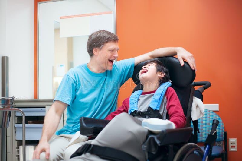 Behinderter kleiner Junge im Rollstuhl sprechend mit Vater im hospita lizenzfreie stockfotos