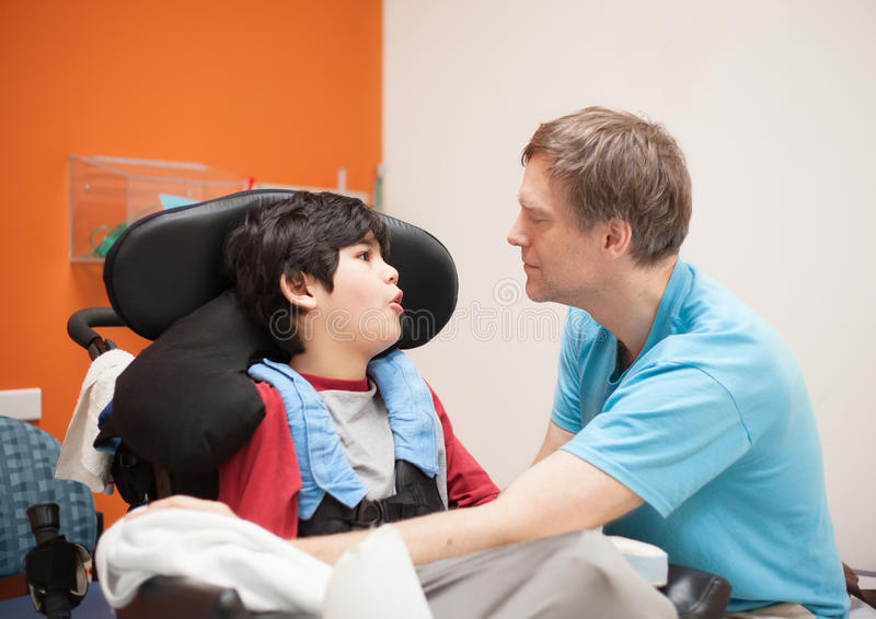 Behinderter kleiner Junge im Rollstuhl sprechend mit Vater im hospita stockbild