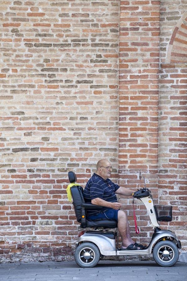 Behinderter Mann auf einem Miniauto vor einer Backsteinmauer stockbild