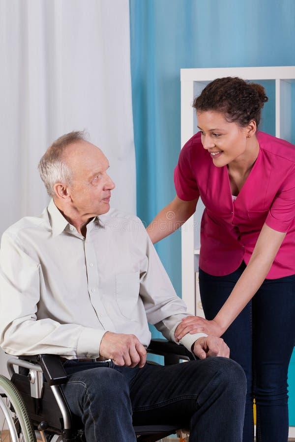 Behinderter Mann auf Rollstuhl und Krankenschwester lizenzfreies stockfoto