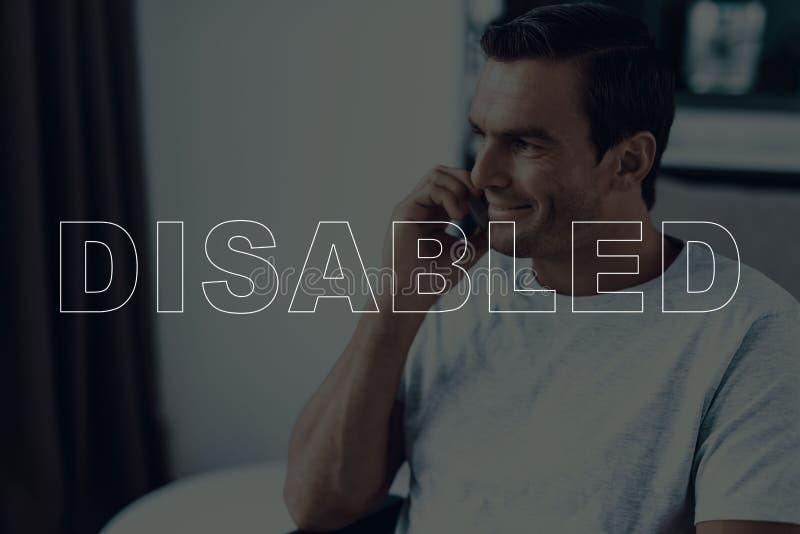 Behinderter Mann in einem Rollstuhl sprechend auf Smartphone stockbilder