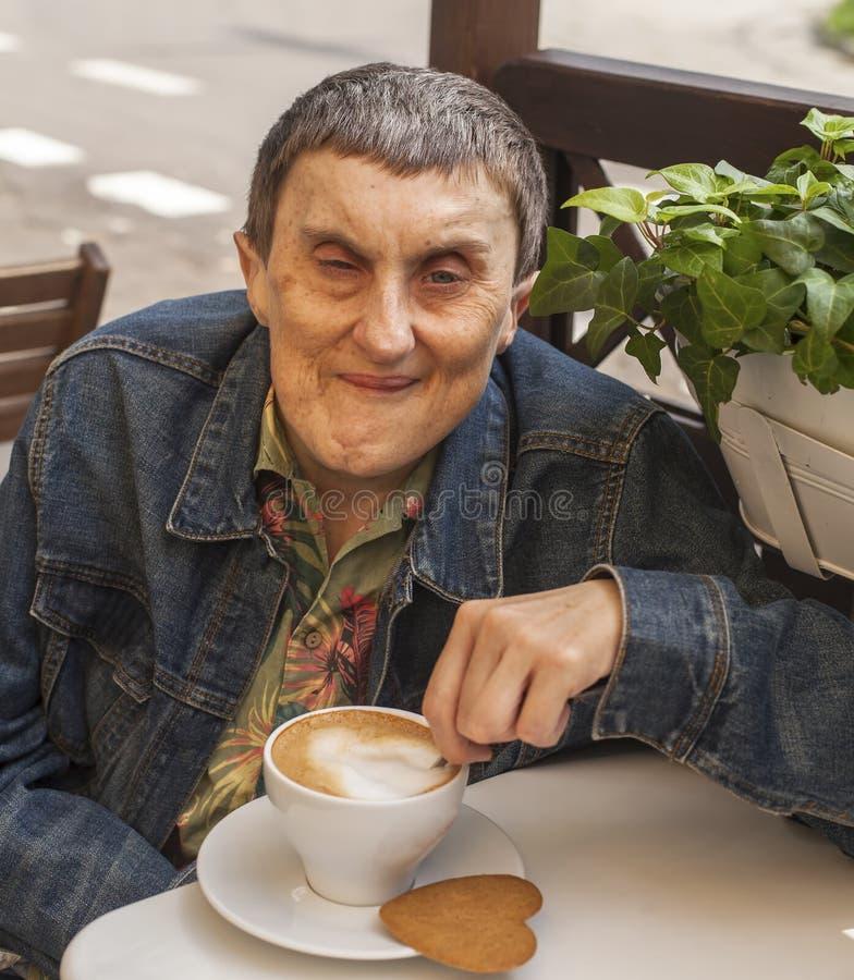 Behinderter Mann mit der Zerebralparese, die Café am im Freien sitzt stockbilder