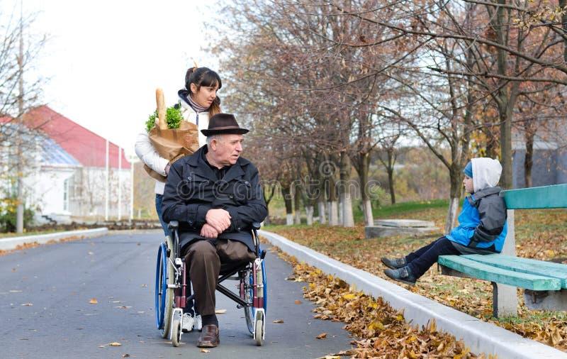 Behinderter Mann und sein Betreuer plaudern zu einem kleinen Jungen stockfoto