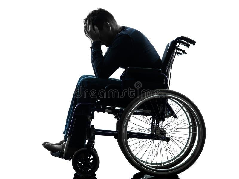 Behinderter Mannkopf in den Händen im Rollstuhlschattenbild lizenzfreies stockfoto