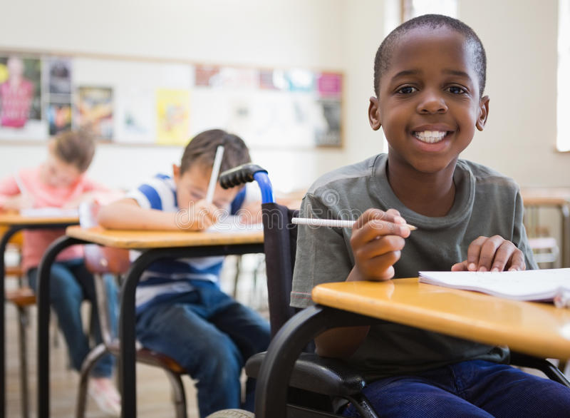 Behinderter Schüler, der an der Kamera im Klassenzimmer lächelt stockfotos