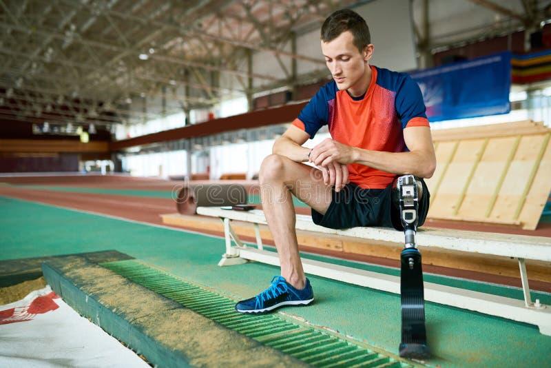Behinderter Sportler, der auf Bank nach der Ausbildung sitzt stockbild