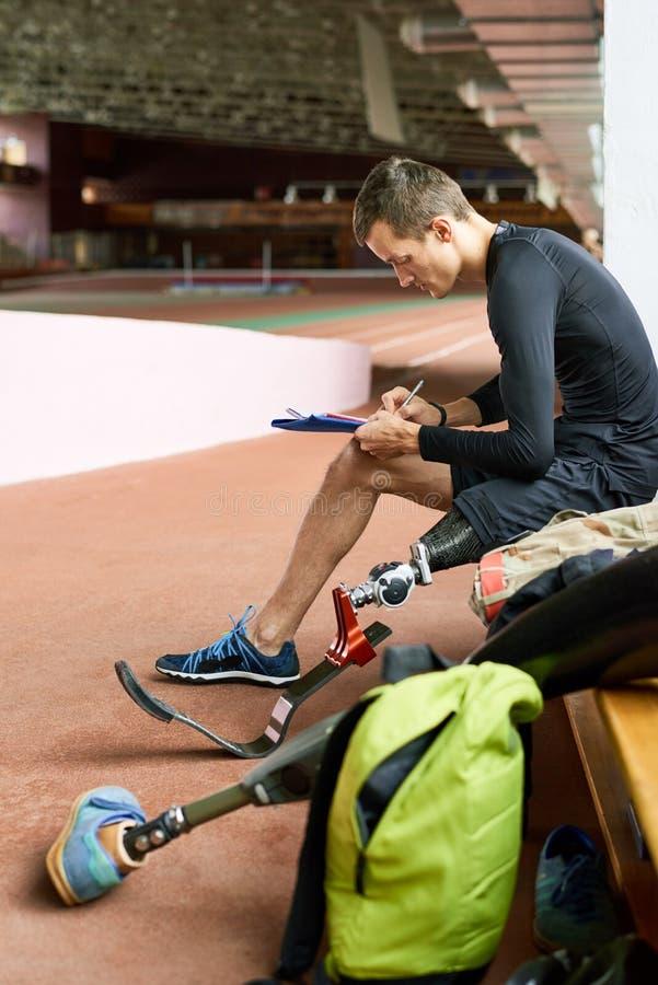 Behinderter Sportler, der auf Bank sitzt lizenzfreie stockbilder
