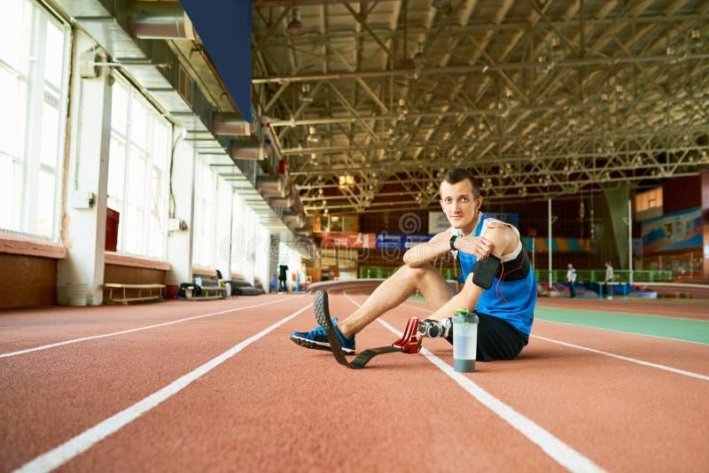 Behinderter Sportler, der auf Laufbahn sitzt lizenzfreies stockfoto