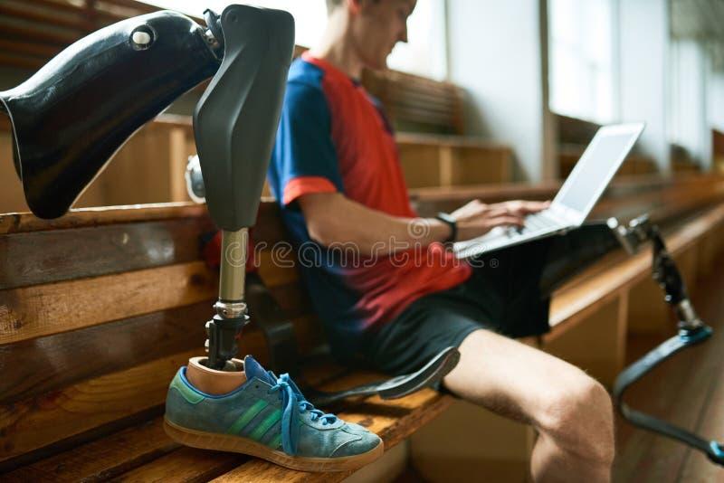 Behinderter Sportler, der Laptop verwendet stockfotografie