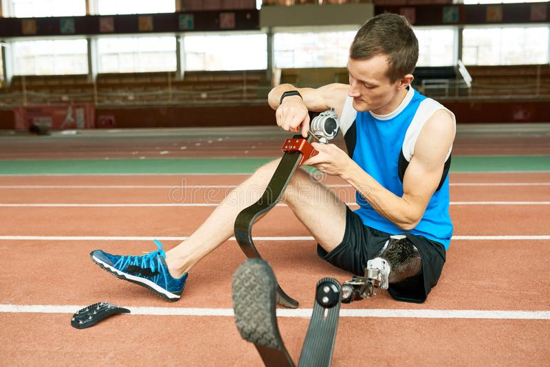 Behinderter Sportler, der prothetischen Fuß repariert lizenzfreie stockfotografie